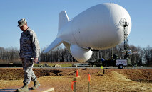 NORAD's Air Force Col. Chuck Douglass walks in front of an unmanned aerostat that is part of a new U.S. military cruise-missile defense system during a media preview, Wednesday, Dec. 17, 2014, in Middle River, Md. Military officials said a pair of helium-filled aerostats stationed in Maryland are intended provide early detection of cruise missiles over a large swath of the East Coast, from Norfolk, Va., to upstate New York, during a three-year test. JLENS, short for Joint Land Attack Cruise Missile Defense Elevated Netted Sensor System, will be fully implemented this winter.