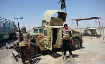 In this file photo, Islamic State group militants stand with a captured Iraqi army Humvee at a checkpoint outside Beiji refinery, around 155 miles north of Baghdad, Iraq.
