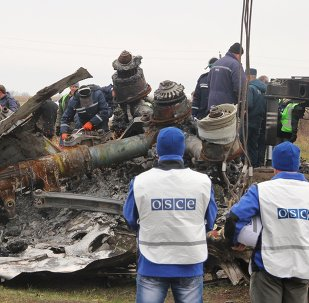 Members of a crew of the Donetsk People's Republic's Emergencies Ministry attempt to saw a gear leg of the Malaysia Airlines Boeing 777