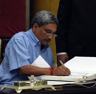 Manohar Parrikar, who resigned Saturday as the chief minister of Goa state signs after taking oath as a new cabinet minister at the presidential palace in New Delhi, India