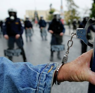 A protester wears handcuffs as he stands in front of riot police following a march during a 24-hour general strike in central Athens November 27, 2014