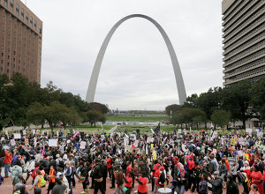 Protesters march past the St. Louis Arch, Saturday, Oct. 11, 2014, in St Louis
