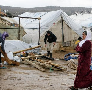 A woman walks past Syrian refugees dismantling their tents at a makeshift settlement in al-Rafid town, in the Bekaa valley