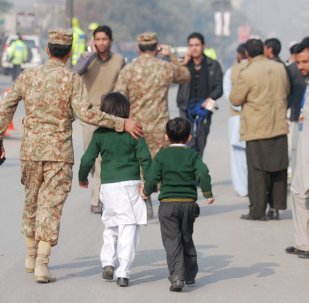 A soldier escorts schoolchildren after they were rescued from the Army Public School that is under attack by Taliban gunmen in Peshawar, December 16, 2014