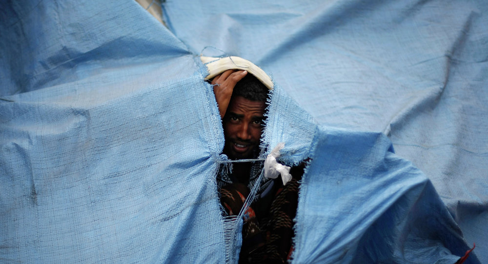 An Eritrean asylum seeker looks through a gap of a temporary shelter on the sidewalk in Sanaa, Yemen