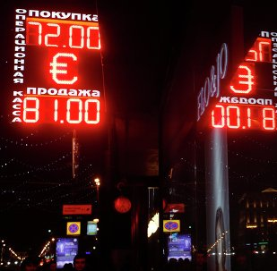 People walk below a board showing currency exchange rates, with a mannequin seen behind a shop window, in central Moscow, December 18, 2014.