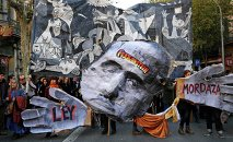 "Demonstrators hold a banner featuring a painting of Pablo Picaso's ""The Guernica"" (back) and a cut-out of former Spanish dictator Francisco Franco (C), during a protest against the Spanish government's new anti-protest security law in Barcelona December 20, 2014."