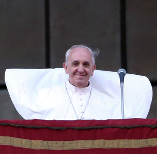 The robes of Pope Francis are blown over his head by a gust of wind as he delivers his blessing from the central balcony of St. John Lateran Basilica on April 7, 2013 in Rome, Italy. The pontiff was formally installed as the Bishop of Rome today, during a mass at the Basilica of Saint John Lateran.
