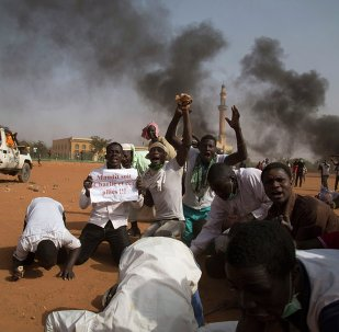 A man (2nd L) holds a sign reading Charlie and his allies are damned during a protest in Niamey Niger, January 17, 2015