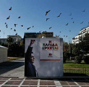 A flock of pigeons flies over a banner with an image of opposition leader and head of radical leftist Syriza party Alexis Tsipras at the party's pre-election kiosk in Athens January 15, 2015.