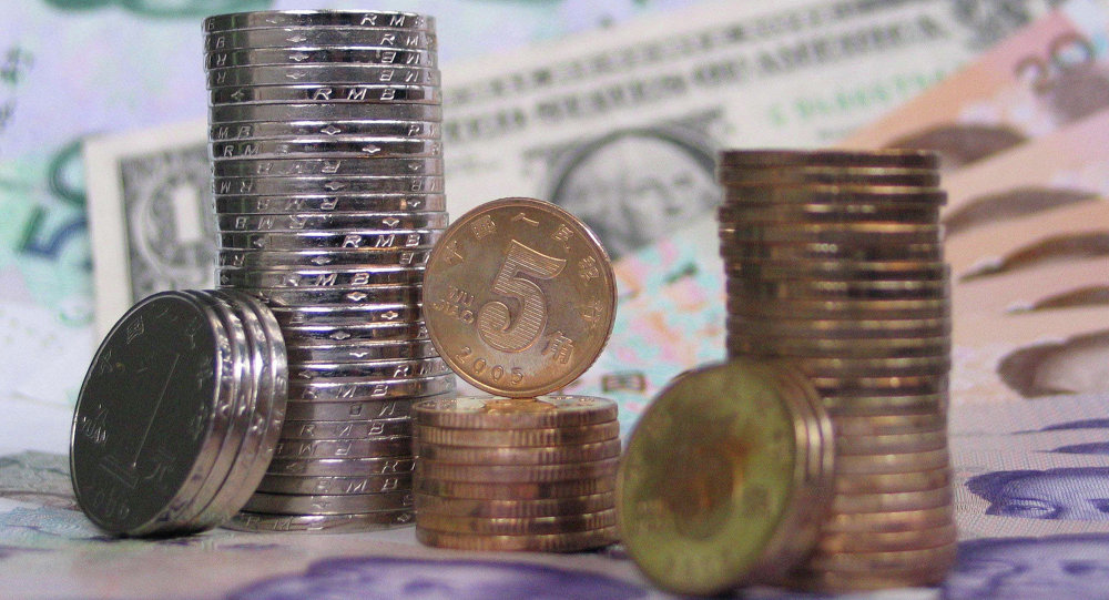 Coins and banknotes of the Chinese yuan are set up together with a U.S. dollar