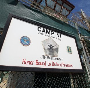 A guard opens the gate at the entrance to Camp VI, a prison used to house detainees at the US Naval Base at Guantanamo Bay
