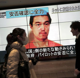 People walk by a screen showing TV news reports of Japanese hostage Kenji Goto, held by the Islamic State group, in Tokyo Saturday, Jan. 31, 2015