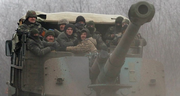 Ukrainian government soldiers ride on a vehicle on the road between the towns of Dabeltseve and Artemivsk, Ukraine, Saturday, February 14, 2015.