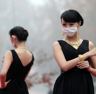 This picture taken on December 7, 2013 shows models wearing surgical masks as they parade a collection of gold jewelleries at a park in Nanjing, east China's Jiangsu province