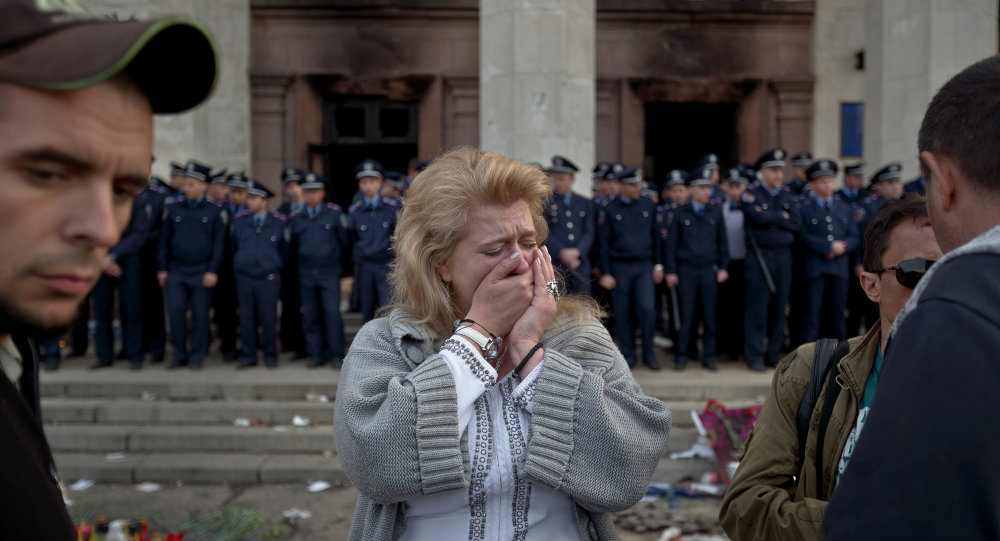 A woman cries back dropped by police troops guarding the burnt trade union building in Odessa, Ukraine, Saturday, May 3, 2014, where more than 30 people died trying to escape during clashes the day before