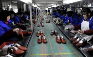 The strengthening dollar and the imbalances in international trade it invoked have become the main source of turbulence for the developing nations. Above: Employees work at a shoe factory in Lishui, Zhejiang province.
