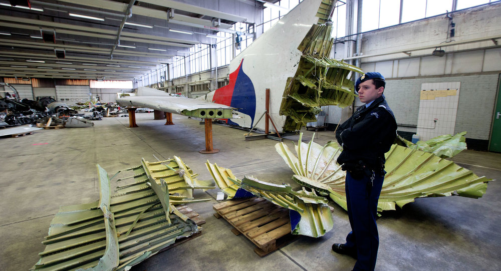 Dutch military police stand next to parts of the wreckage of the Malaysia Airlines Flight 17, displayed in a hangar at Gilze-Rijen airbase, Netherlands, Tuesday, March 3, 2015