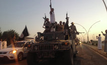 ISIL fighters parade through Mosul, Iraq in 2014.
