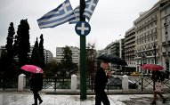 People holding umbrellas make their way next to fluttering Greek national flags on the main Constitution (Syntagma) square during heavy rainfall in Athens