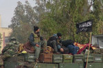 Rebels from al-Qaida affiliated al-Nusra Front, as they sit on a truck full of ammunition, at Taftanaz air base, that was captured by the rebels, in Idlib province, northern Syria