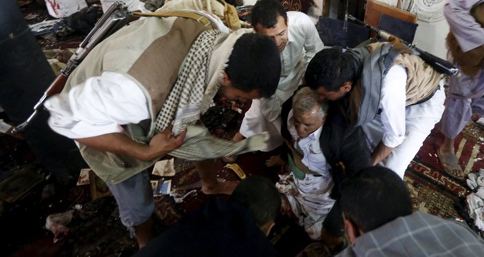 People help an injured man at the scene of a suicide bombing inside a mosque in Sanaa March 20, 2015