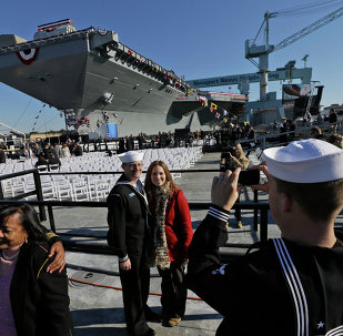People pose for photos in front of Navy aircraft carrier USS Gerald R. Ford during the christening of the ship in November 2013.