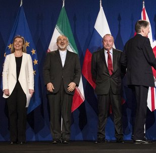 (L-R) European Union High Representative for Foreign Affairs and Security Policy Federica Mogherini, Iranian Foreign Minister Javad Zarifat and an unidentified Russian official look on as British Foreign Secretary Philip Hammond shakes hands with U.S. Secretary of State John Kerry, following nuclear talks at the Swiss Federal Institute of Technology in Lausanne