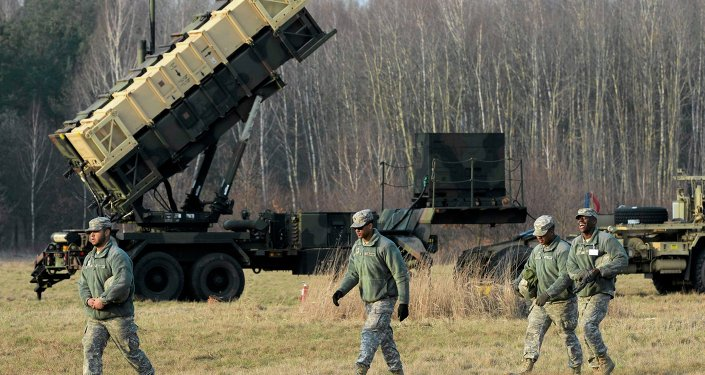 U.S soldiers walk next to a Patriot missile defence battery during join exercises at the military grouds in Sochaczew, near Warsaw