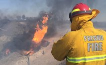 A firefighter watches the blaze after a gas line exploded near Fresno, California