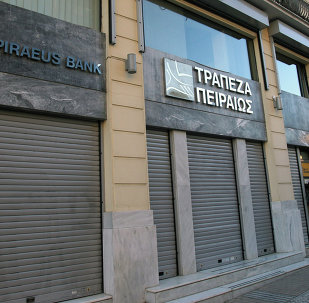 A man uses an ATM of Piraeus Bank in central Athens.