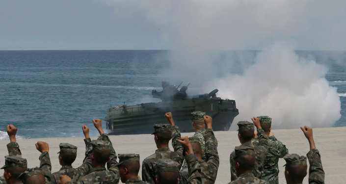 Philippine Marines cheer as a U.S. Navy AAV (Amphibious Assault Vehicle) storms the beach during a combined assault exercise facing one of the contested islands in the South China Sea.