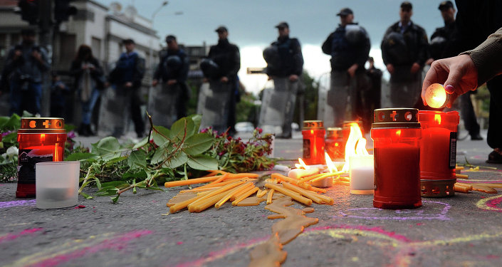 People light candles in front of the riot policemen to commemorate policemen who were killed after fighting between Macedonian police and an armed group in the town of Kumanovo , in Skopje on May 11, 2015