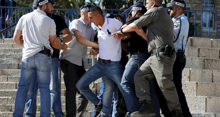 Israeli police officers scuffle with a Palestinian protester (C) as they disperse a protest near Damascus Gate outside Jerusalem's Old City, during a march marking Jerusalem Day, May 17, 2015