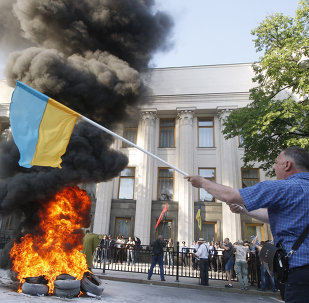 Protesters burn tires during a rally supporting a law on the restructuring of foreign currency loans in front of the Ukrainian Parliament in Kiev on May 21, 2015