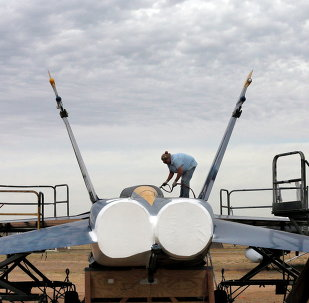 Preservation servicer Katy Shank sprays a sealing paint on a former NAVY Blue Angel F-18 at the 309th Aerospace Maintenance and Regeneration Group boneyard in Tucson, Ariz