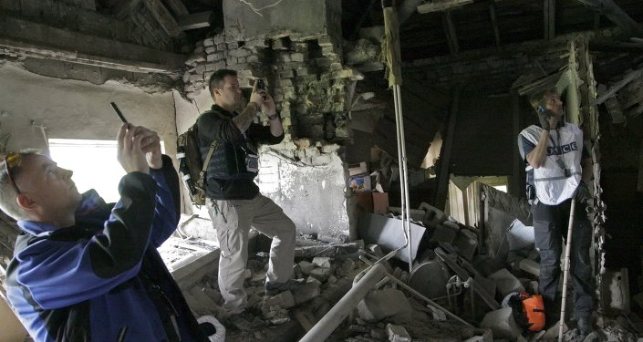 Members of the Organization for Security and Co-operation in Europe (OSCE) work within the ruins of a residential building, which according to locals was recently damaged by shelling, in Donetsk, Ukraine