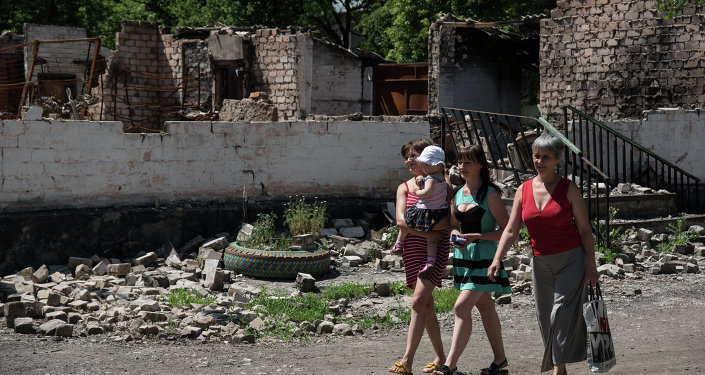 Residents walk in front of destroyed building as a result of shelling on June 8, 2015 in Novotoshkivske village, Donetsk region