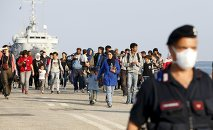 Syrian refugees are escorted by Carabinieri after disembarking from Belgian Navy vessel Godetia at the Augusta port, Italy, June 10, 2015