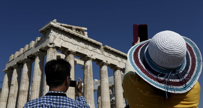 Visitors take pictures in front of the Parthenon temple atop the Acropolis hill in Athens