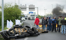 Striking ferry workers burn tyres as they block a ramp leading into the Eurotunnel before being dispersed by riot police in Calais, northern France, Tuesday, June 23, 2015