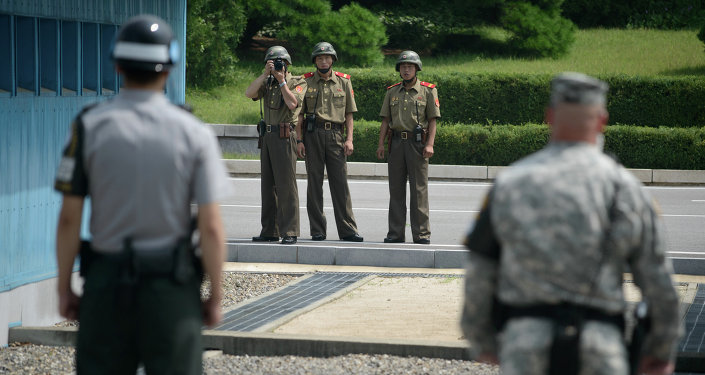 North Korean soldiers (C) take photos towards a South Korean soldier (L) and a US soldier (R) standing before the military demarcation line (lower C) seperating North and South Korea within the Joint Security Area (JSA) at Panmunjom on July 27, 2014
