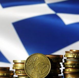 Euro coins are seen in front of a displayed Greece flag
