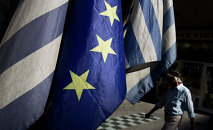 A man walks past a European and Greek flags in central Athens, on Tuesday, June 30, 2015.