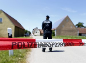 A police tape and a German police officer are seen in Tiefenthal near Ansbach, Germany, July 10, 2015