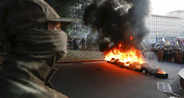 Tyres are set on fire during a rally held by members of the far-right radical group Right Sector, representatives of the Ukrainian volunteer corps and their supporters in central Kiev, Ukraine, July 3, 2015