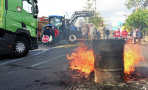 A barrel burns as a road in Kehl, Germany is blocked by French farmers leading to a bridge linking Kehl and Stasbourg, France on July 27, 2015