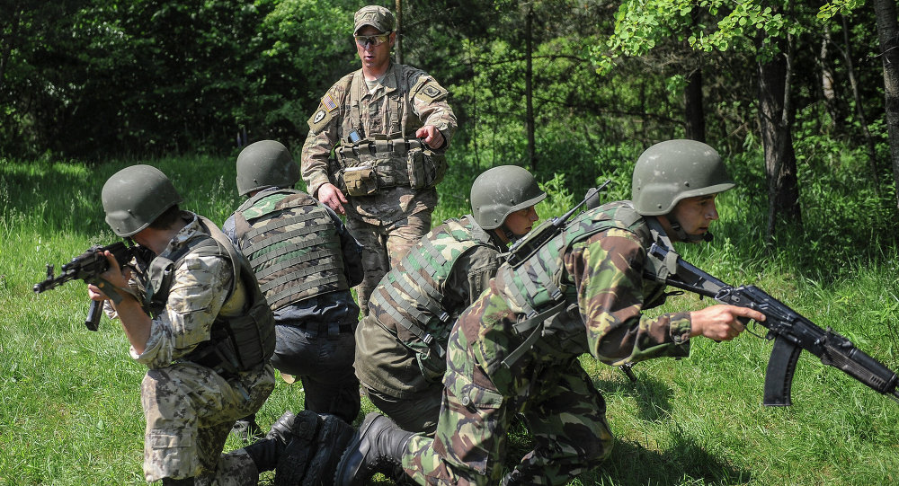 US soldier, center, instructs Ukrainian soldiers during joint training exercises on the military base in the Lviv region, western Ukraine