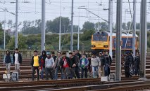 Migrants make their way along train tracks as they attempt to access the Channel Tunnel in Frethun, near Calais, France, July 29, 2015