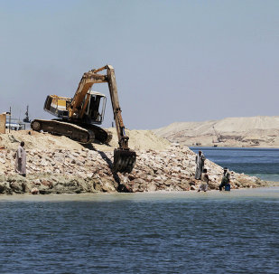 A bulldozer works on the new section of the Suez Canal in Ismailia, Egypt, Wednesday, July 29, 2015